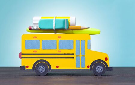 Back to school concept. Paper-cut model yellow school bus on colour background