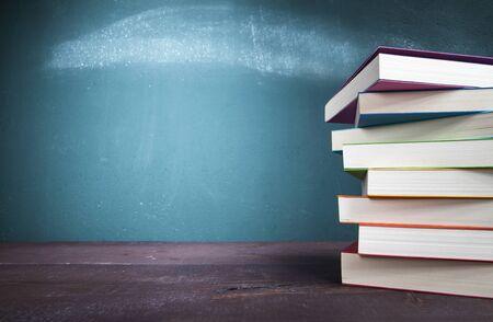 Textbooks on school desk with blackboard. Back to school concept. Stok Fotoğraf - 128815779