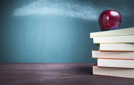 Textbooks and an apple on school desk with blackboard. Back to school concept.