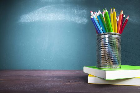 Textbooks and pencil holder on school desk with blackboard. Back to school concept. Stok Fotoğraf