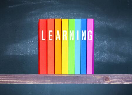 Learning concepts, colourful books on wooden table with blackboard