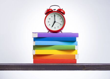 Stack of colored books and alarm clock on wooden table. Back to school concept.
