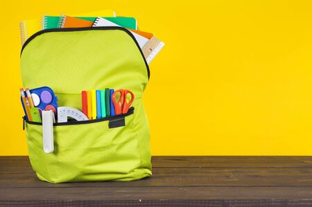 Full school backpack on wooden and bright yellow background