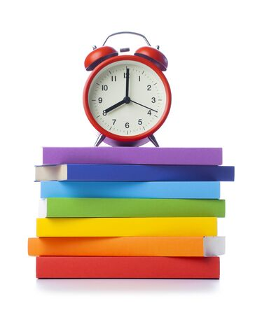 Stack of colored books with alarm clock on white background Stok Fotoğraf - 128816019