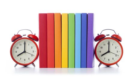 Group of colored books with alarm clocks on both sides