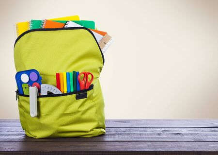 Full school backpack on wooden and beige background