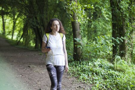 Young woman walking in park and listening to music Stok Fotoğraf