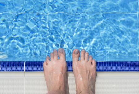 Bare feet over swimming pool on summer day