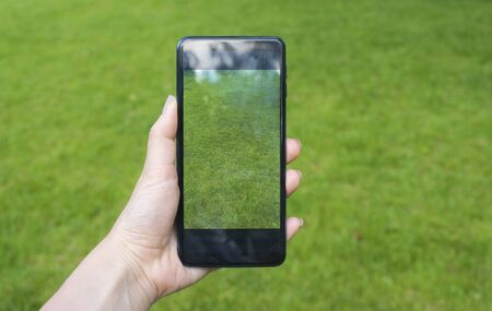 Woman hand holding green grass screen smartphone in park
