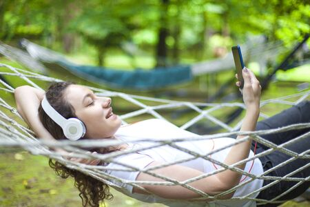 Young woman wearing headphones and relaxing on vacations in tropical garden