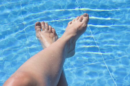 Womans feet against blue water of the pool