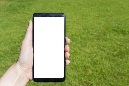 Woman hand holding blank screen smart phone in park