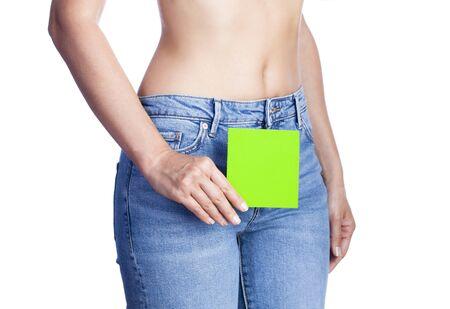 Mujer joven sosteniendo un libro verde en su cintura. Concepto de salud. Higiene, menstruación. Salud del sistema vaginal o urinario.