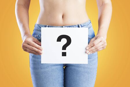 Young woman holding a paper with question mark on her waist. Vaginal or urinary infection and problems concept. Stok Fotoğraf