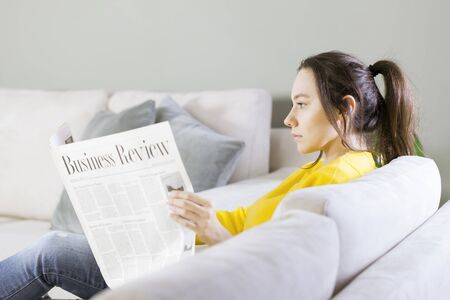 Young beautiful brunette woman reading newspaper sitting on sofa 写真素材