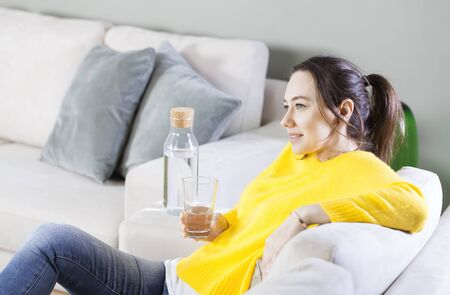 Young woman drinking water sitting on a couch at home