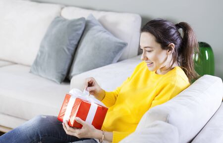 Young woman with gift for Valentines Day or her birthday at home
