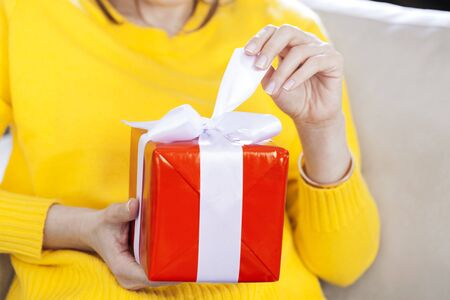 Hand pulls white ribbon on a gift wrapped in red paper Stok Fotoğraf