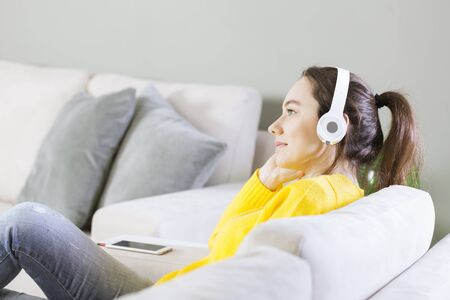 Portrait of a beautiful young woman sitting on sofa with headphones
