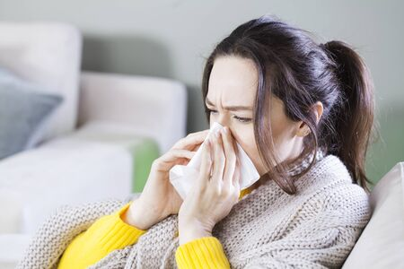 Young sick woman sitting on sofa in living room covered with blanket and wiping nose with tissue paper