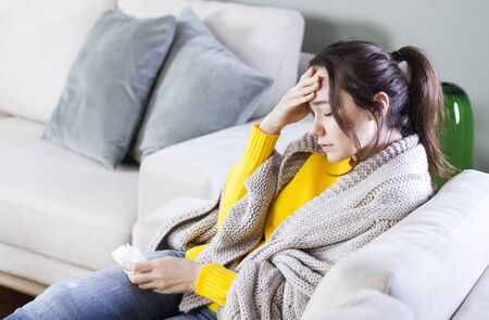 Young woman with headache sitting on sofa. She holding a handkerchief to wipe her nose