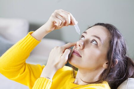 Young woman uses eye drops for eye treatment. Redness, Dry Eyes, Allergy and Eye Itching