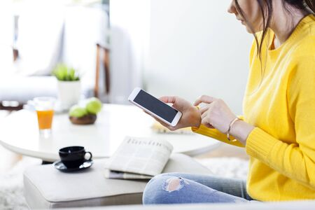 Young woman using smartphone while sitting at home and communicate with friends in social networks, female freelancer working from home 写真素材