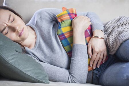 Young woman in painful expression, holding hot water bottle against belly suffering menstrual period pain lying down on sofa having tummy cramp Stok Fotoğraf