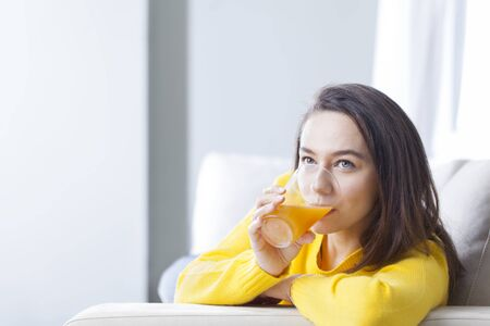 Young woman drinking orange juice at home