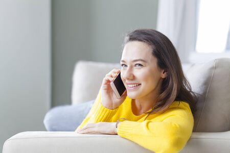Happy young woman talking on the phone at home, lying down on sofa