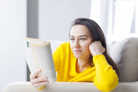 Young woman resting on sofa and reading a book  Stock Photo