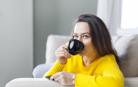 Young woman sit down on the sofa drinking coffee for morning routine at home. Leisure activity, lifestyle for people concept.