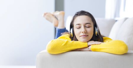 Young woman lying on sofa listening to music with headphones and relaxing at home.
