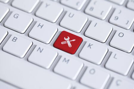 Red key with work tools icon on white laptop keyboard Stok Fotoğraf