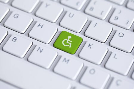 Green key with wheelchair icon on white laptop keyboard. Accessibility disability computer symbol