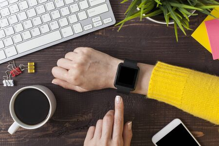 Businesswoman using smartwatch while working at office, woman touching on smartwatch screen. 写真素材