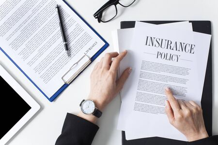 Business woman showing insurance document over white desk at office