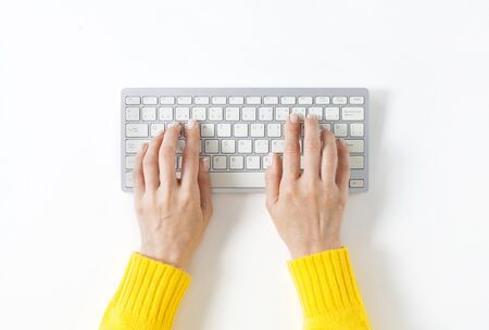 Top view on female elegant hands on a computer keyboard. Isolated white background and clipping path. Simple design, large copy space for your designs