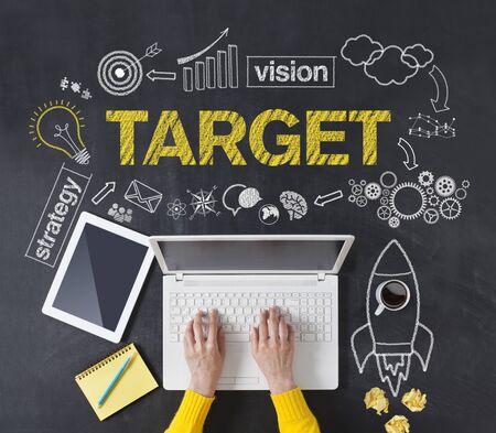 Business goals concept with hands typing laptop on the blackboard background.