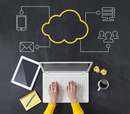 Cloud computing concept with hands typing laptop on the blackboard background.