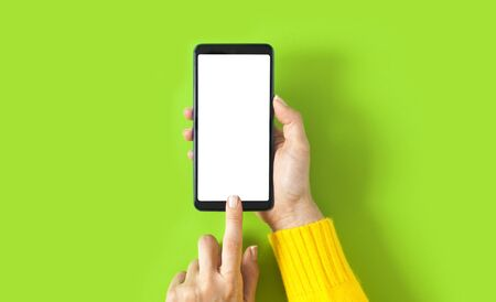 Female hand holding smartphone with blank screen on green background. Mockup template for your design. Stok Fotoğraf