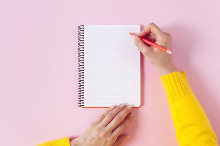 Female hand writing in a blank spiral notepad on pink background. Mockup for design. Young woman write diary or a to do list. 写真素材