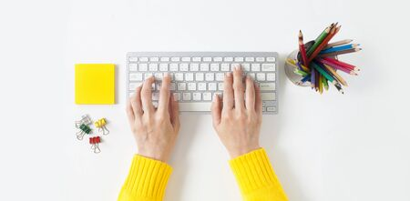 Top view on female elegant hands on a computer keyboard. Isolated white background. Simple design, large copy space for your designs