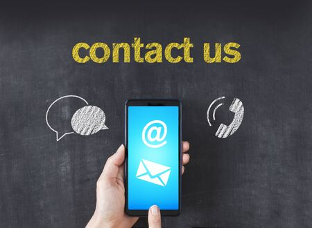 Hand holding smartphone with Contact Us written on blackboard