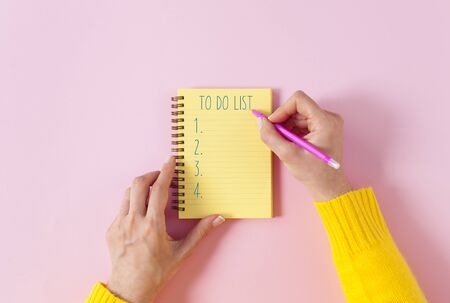 To do list in spiral notepad. Woman hands making to do list in notebook. Spiral notepad with pencil as mockup for design