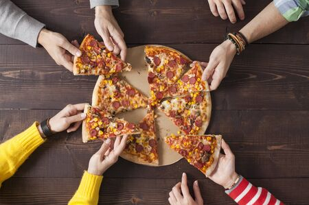 Top view shot of a group of peoples hands each grabbing a slice of pizza 写真素材