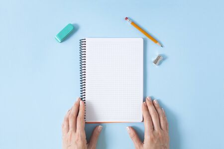 Womans hands holding a spiral notepad as mockup for your design. Blue pastel background and few office supplies