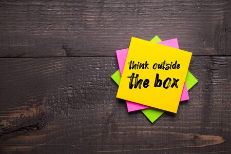 Multi-colored stickers with Think Outside The Box message on wooden background. Business concept, strategy, plan, planning.