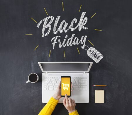 Black friday advertisement on blackboard. Woman shopping with smart phone app. Online e-commerce shopping concept.