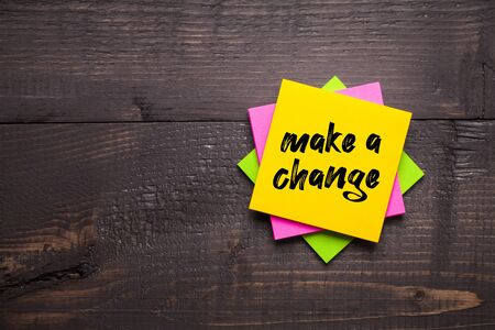 Multi-colored stickers with Make a Change message on wooden background. Business concept, strategy, plan, planning.